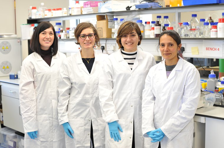Maria Teresa and her team in their research lab in lab coats